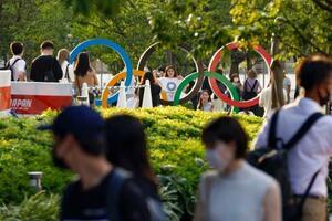 国立競技場近くの五輪マークのモニュメントを囲む人たち。新たな新型コロナウイルス感染者は、全国でも東京都内でも過去最多が報告された=28日午後5時48分、東京都新宿区