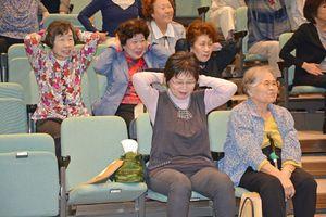 椅子に座ったままできるロコモ体操を体験する参加者=佐賀市のメートプラザ佐賀