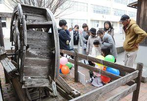 壊れた水車を飾り付けて製作当時を懐かしむ元6年1組のクラスメートや当時の教諭ら=神埼市の仁比山小