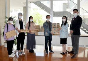 支援物資を受け取る留学生ら=佐賀市の西九州大短大部
