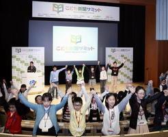 「こども新聞サミット」のオープニングで全員で手をつなぎ「さあ、未来を動かそう」と宣言するこども記者たち=3日午後、東京都江東区の日本科学未来館