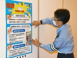 ワクチン接種会場で交通安全を呼び掛けるポスターを張る鳥栖署員=上峰町民センター