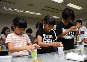 牛乳からバイオプラスチックを作る子どもたち=佐賀市天神のアバンセ