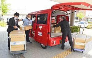 新型コロナウイルスのワクチン接種券を積み込む郵便局員ら=19日午後、佐賀市のほほえみ館
