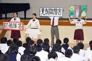 紙芝居で認知症の症状などについて解説する神埼清明高の生徒=みやき町の中原中