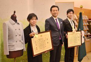 技能グランプリで内閣総理大臣賞に輝いた金武節子さん(左)と敢闘賞を獲得した植松健一さん(右)。山口祥義知事から賞状を受け取った=県庁