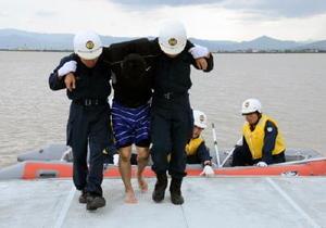 ゴムボートから水難者役を陸に引き上げる白石署員ら=白石町の遊水池