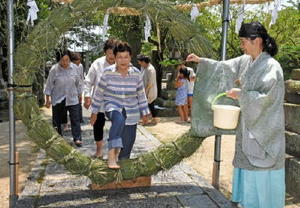 みそぎを受けて茅の輪をくぐる人たち=鳥栖市本鳥栖町の水影天神社