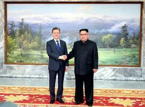 26日、板門店で会談に先立ち握手する韓国の文在寅大統領(左)と北朝鮮の金正恩朝鮮労働党委員長(韓国大統領府提供・共同)
