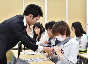洋服の青山佐賀本店の平野和也さん(左)からネクタイの結び方を学ぶ生徒=佐賀市のKTC中央高等学院佐賀キャンパス