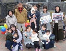 水車を前に記念撮影する製作メンバーや当時の教諭ら=神埼市の仁比山小
