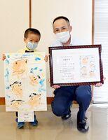 最優秀賞の家族の絵を持ち笑顔を見せる川〓田隼也ちゃん。右は父の茂昭さん=佐賀市の佐賀新聞社