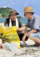 民泊などを通し、今帰仁村の魅力を伝えている相原実里さん(左)=沖縄県今帰仁村仲宗根の村民の浜