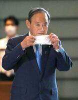 マスクを手に首相官邸に入る菅首相=17日午前
