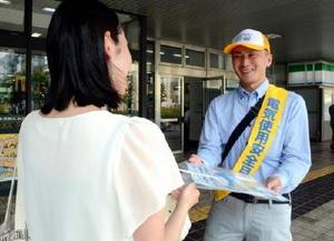 JRの利用者へうちわやチラシを配り、電気の安全な利用を呼び掛ける組合理事=佐賀市のJR佐賀駅
