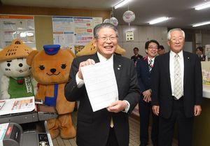 キオスク端末を使用して住民票の取得し、笑顔を見せる松本茂幸市長=神埼市脊振町の脊振郵便局