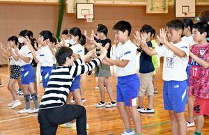 東京都のパントマイム劇団「汎(はん)マイム工房」によるワークショップで、見えない壁をパントマイムで表現する春日小の児童たち=佐賀市の同小(22日付17面)