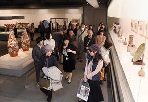 学芸員の解説を聞きながら作品を鑑賞する来場者=佐賀市の県立博物館