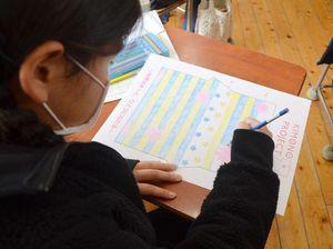 国旗の青と黄色や星、桜をモチーフに着物の図案を描く児童=1月30日、佐志小
