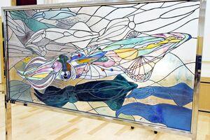 イカ画家の宮内裕賀さんがデザインしたステンドグラス=唐津市呼子町の呼子公民館