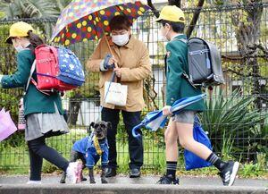 飼い主の大坪都子さん(右から2人目)と児童の登校を見守るシュン君=神埼市の神埼小