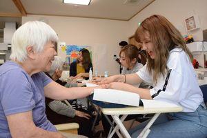 学生が施すマッサージに笑顔を見せる入居者=神埼市神埼町のグループホーム神埼ひだまり新館