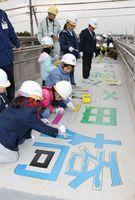 歩道橋の床に「未来への架け橋~希里橋」と描く基里小の子どもたち=鳥栖市曽根崎町