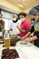 ローゼルの茎などから取った染料でマスクを染めるISUZUプロジェクトのメンバーたち=唐津市高島の高島公民館