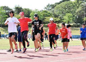 基礎練習で汗を流す選手たち=伊万里市の国見台陸上競技場