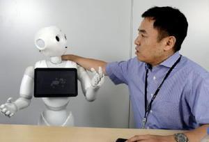 ソフトバンクロボティクスの蓮実一隆さんと人型ロボット「Pepper」=東京都港区