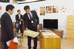 全国から集まるバイヤーに商品説明する門田陽一社長(右)=福岡県大川市の大川産業会館