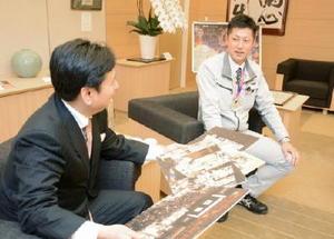山口祥義知事(左)にパネル写真を見せながら大会について報告する電興社の小栁剛之さん=県庁