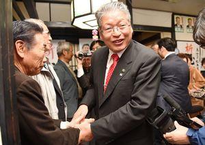 4選を果たし、支持者と握手を交わす松本茂幸さん(中央)=15日午後10時12分、神埼市神埼町田道ケ里の事務所