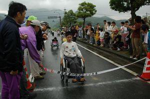 雨の中、車いすで力走する選手たち=有田町の県道大木―有田線