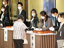 九州電力の株主総会が開かれたホテルで、受付をする株主。新型コロナウイルスの感染拡大を踏まえ、予防策が講じられた=福岡市(代表撮影)