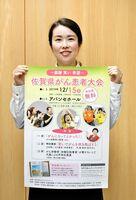 大会のポスターを手にするクレブスサポートボランティアスタッフの嘉村幸さん=佐賀新聞社