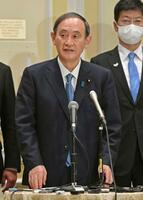 記者団の取材に応じる菅首相=16日、ワシントン(共同)