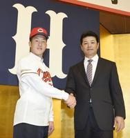 広島の新入団記者会見で、緒方監督(右)と握手するドラフト1位の小園海斗内野手=10日、広島市