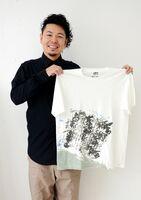 自身の作品「一歩」をあしらったユニクロのTシャツを掲げる書道家の山口芳水さん=佐賀市のNOART(ノーアート)