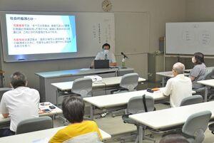 研修会で、児童養護施設の取り組みなどの説明を受ける参加者=佐賀市のアバンセ
