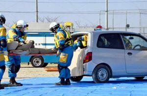 水没した車両に閉じ込められた人を助け出す機動隊員ら=佐賀市久保田町の思斉館中学部グラウンド