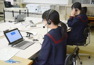 英語の予備調査で、マイクを使って回答する中学生=唐津市小川島の小川小中校