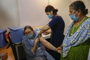 インド・ムンバイで新型コロナウイルスのワクチン接種を受ける女性(左)=22日(AP=共同)