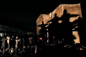 阪神大震災から24年となるのを前に、ライトアップで人影が鎮魂の十字架として映し出された「神戸の壁」=12日夜、兵庫県淡路市の北淡震災記念公園