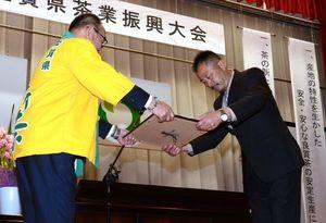 県茶共進会「荒茶の部」で最優秀賞となり、表彰状を受け取る橋爪和広さん(右)=嬉野市公会堂