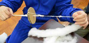 手製の糸繰り車を使用して綿から糸を作り出した