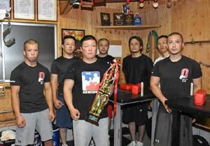 九州アームレスリング大会で2階級優勝、2階級準優勝を果たした柴田和弘さん(左から3人目)とチーム「男腕」の仲間たち=伊万里市大坪町の自宅トレーニング場