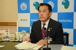 定例会見で3月議会の機構改革案撤回について説明する峰達郎市長=唐津市役所
