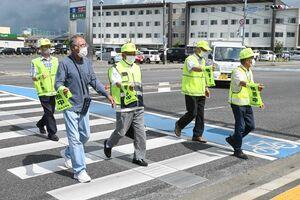 携帯用横断旗を使用する佐賀市老人クラブ連合会の会員=同市の佐賀南署付近
