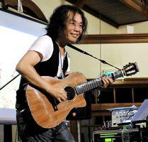 特注したベフニックギターでオリジナルソング「アジサイ」を演奏する小倉博和さん=佐賀市柳町の浪漫座 (昨年10月)
